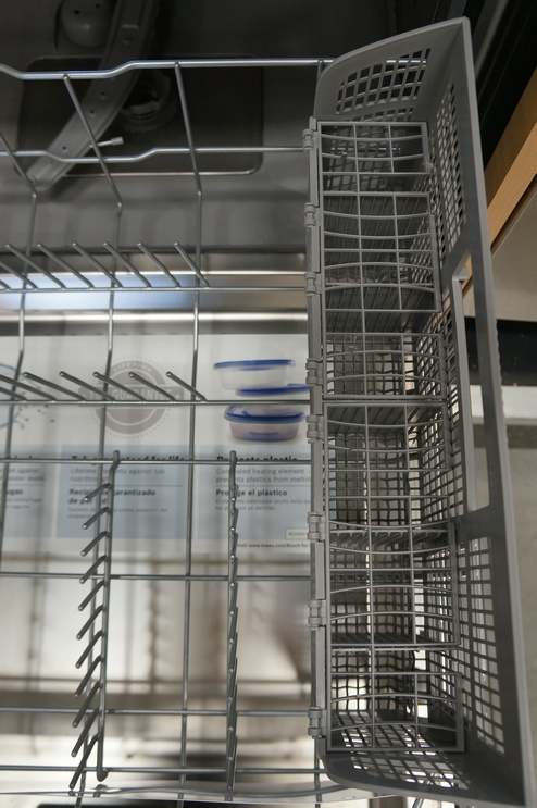 The lower rack has fixed tines and a removable silverware basket.