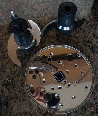 "The Oster comes with a multipurpose ""S"" blade, reversible slicing/shredding disc, and a dough blade."